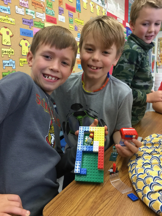 Two students holding a lego construction